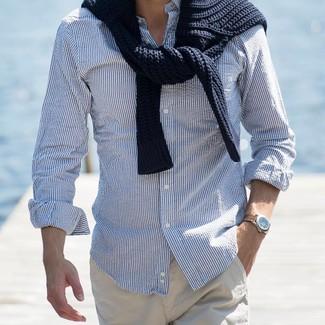 Wie kombinieren: schwarzer Strickpullover, weißes und blaues vertikal gestreiftes Langarmhemd, hellbeige Chinohose
