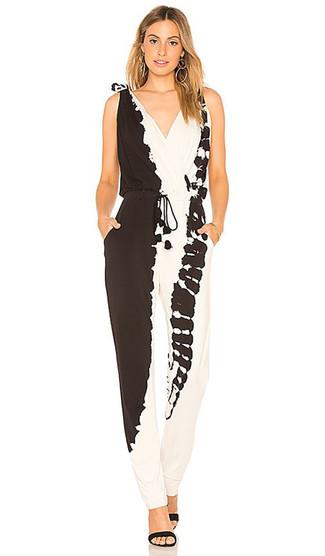 Wie kombinieren: schwarzer und weißer Mit Batikmuster Jumpsuit, schwarze Wildleder Sandaletten, goldene Ohrringe
