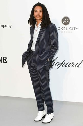 Wie kombinieren: schwarzer und weißer vertikal gestreifter Anzug, weißes und schwarzes vertikal gestreiftes Langarmhemd, weiße Cowboystiefel aus Leder