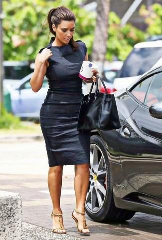 Kim Kardashian trägt Schwarzes Figurbetontes Kleid, Goldene Leder Sandaletten, Schwarze Shopper Tasche aus Leder
