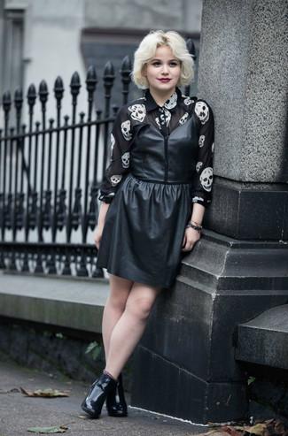 Wie kombinieren: schwarzes Leder Trägerkleid, schwarzes und weißes bedrucktes Chiffon Businesshemd, schwarze Leder Stiefeletten