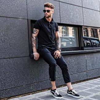 Wie kombinieren: schwarzes Polohemd, schwarze Chinohose, schwarze und weiße Segeltuch niedrige Sneakers