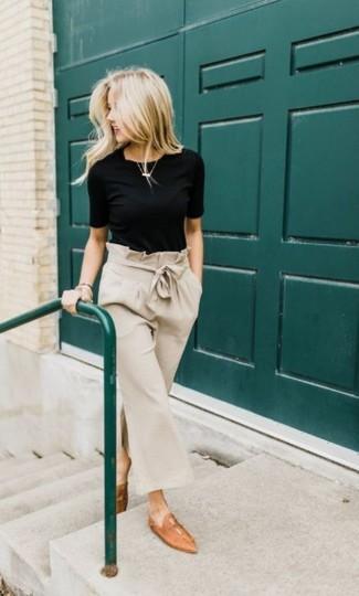 Wie kombinieren: schwarzes T-Shirt mit einem Rundhalsausschnitt, hellbeige Hosenrock, beige Leder Slipper