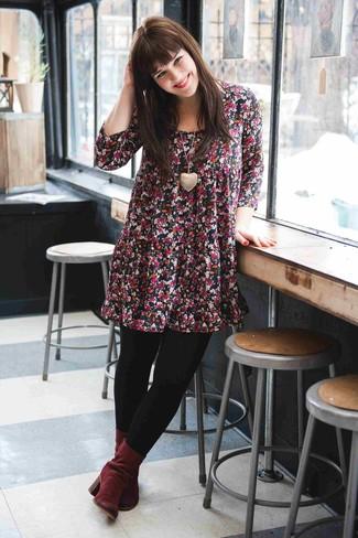 Wie kombinieren: schwarzes schwingendes Kleid mit Blumenmuster, dunkelrote Wildleder Stiefeletten, goldener Anhänger, schwarze Wollstrumpfhose