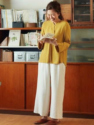 Braune Leder Slipper kombinieren: trends 2020: Wer perfekt aber locker gekleidet sein will, setzt oft auf mühelose Outfits, wie zum Beispiel diese Paarung aus einer senf Langarmbluse und einer weißen weiter Hose. Braune Leder Slipper sind eine großartige Wahl, um dieses Outfit zu vervollständigen.