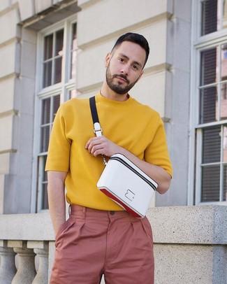 Wie kombinieren: senf Strick T-Shirt mit einem Rundhalsausschnitt, rosa Chinohose, weiße Bauchtasche