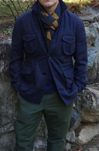 Wie kombinieren: dunkelblaue Wollshirtjacke, dunkelblauer Pullover mit einem Rundhalsausschnitt, dunkelgrüne Chinohose, dunkelblauer bedruckter Schal