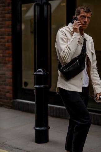 Wie kombinieren: hellbeige Shirtjacke, weißes T-Shirt mit einem Rundhalsausschnitt, schwarze Chinohose, schwarze Leder Bauchtasche