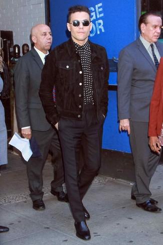 Rami Malek trägt schwarze Shirtjacke aus Cord, schwarzes und weißes Langarmhemd mit Sternenmuster, schwarze Anzughose, schwarze Chelsea-Stiefel aus Leder