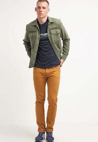 Wie kombinieren: olivgrüne Shirtjacke, schwarzes und weißes bedrucktes T-Shirt mit einem Rundhalsausschnitt, senf Jeans, dunkelblaue niedrige Sneakers