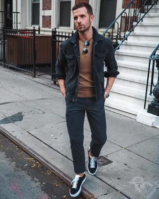 Wie kombinieren: schwarze Shirtjacke aus Cord, brauner Pullover mit einem Rundhalsausschnitt, schwarze Chinohose, schwarze und weiße Segeltuch niedrige Sneakers