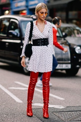 Wie kombinieren: weißes und schwarzes gepunktetes Shirtkleid, rote Overknee Stiefel aus Leder, schwarze Pelz Umhängetasche, schwarzer Taillengürtel