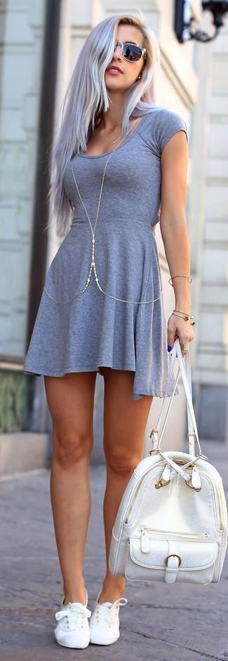 Grauen Leder Rucksack kombinieren – 12 Damen Outfits: Ein graues Skaterkleid und ein grauer Leder Rucksack sind eine richtig schöneKombi, die siehtsehr lässig aus. Vervollständigen Sie Ihr Look mit weißen niedrigen Sneakers.