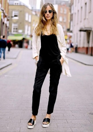 Wie kombinieren: weißer Staubmantel, schwarzer Jumpsuit, schwarze und weiße flache Sandalen aus Leder, schwarze Sonnenbrille