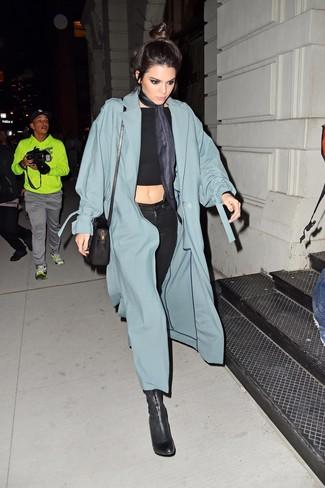 dunkeltürkiser Staubmantel, schwarzes kurzes Oberteil, schwarze enge Jeans, schwarze Leder Stiefeletten für Damen