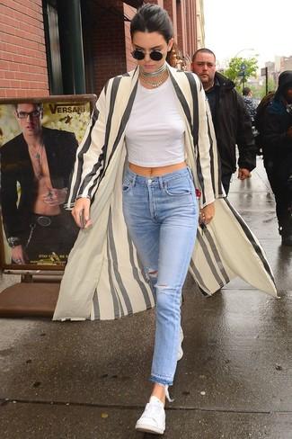 Wie kombinieren: hellbeige vertikal gestreifter Staubmantel, weißes kurzes Oberteil, hellblaue Jeans mit Destroyed-Effekten, weiße niedrige Sneakers