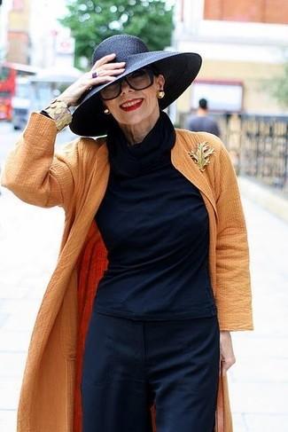 Wie kombinieren: orange Staubmantel, dunkelblauer Rollkragenpullover, dunkelblaue weite Hose, schwarzer Strohhut