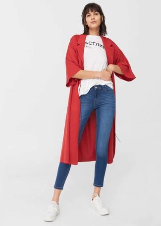 roter Staubmantel, weißes und schwarzes bedrucktes T-Shirt mit einem Rundhalsausschnitt, blaue enge Jeans, weiße niedrige Sneakers für Damen