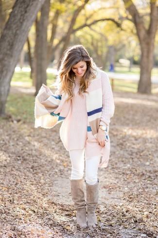 Wie kombinieren: mehrfarbige horizontal gestreifte Stola, rosa Strick Rollkragenpullover, weiße enge Jeans, hellbeige kniehohe Stiefel aus Wildleder
