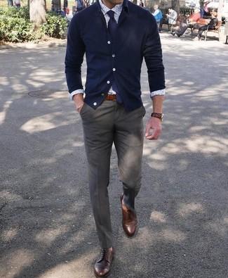 Wie kombinieren: dunkelblaue Strickjacke, weißes bedrucktes Businesshemd, olivgrüne Anzughose, dunkelbraune Leder Derby Schuhe