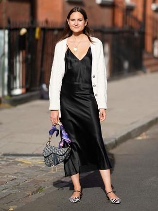 Wie kombinieren: weiße Strick Strickjacke, schwarzes Camisole-Kleid aus Satin, weiße und schwarze Leder Ballerinas, graue bedruckte Satchel-Tasche aus Segeltuch