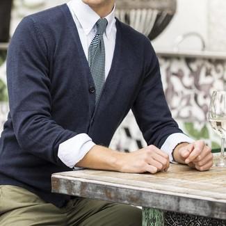 Wie kombinieren: dunkelgraue Strickjacke, weißes vertikal gestreiftes Businesshemd, beige Chinohose, schwarze Krawatte mit Karomuster