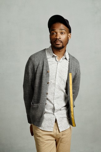 Wie kombinieren: graue Strickjacke, graues Langarmhemd mit Blumenmuster, beige Chinohose, schwarze Baseballkappe