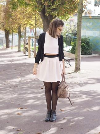 Wie kombinieren: schwarze Strickjacke, weißes kurzes Oberteil, weißer Falten Minirock, schwarze Leder Stiefeletten