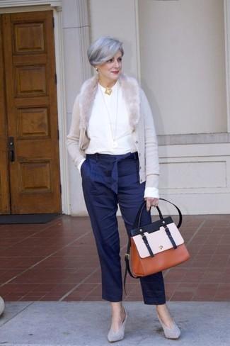 60 Jährige: Outfits Damen 2020: Die Kombination aus einer grauen Strickjacke und einer dunkelblauen vertikal gestreiften Karottenhose ist ideal für die Freizeit geeignet. Dieses Outfit passt hervorragend zusammen mit grauen Wildleder Pumps.