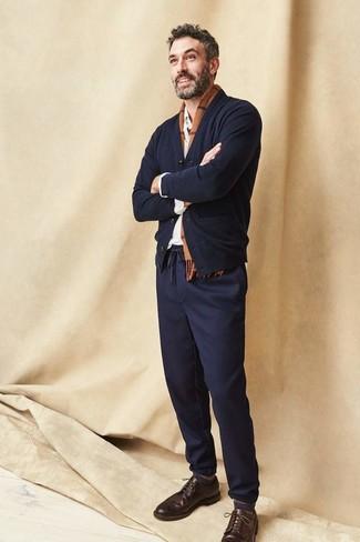Wie kombinieren: schwarze Strickjacke, weißes Langarmhemd, dunkelblaue Chinohose, dunkelbraune Leder Brogues