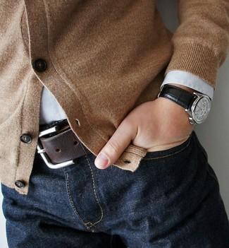 Wie kombinieren: beige Strickjacke, weißes Langarmhemd, dunkelblaue Jeans, dunkelbrauner Ledergürtel