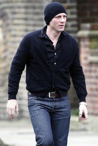 Daniel Craig trägt schwarze Strickjacke, schwarzes Langarmhemd, dunkelblaue Jeans, schwarze Mütze