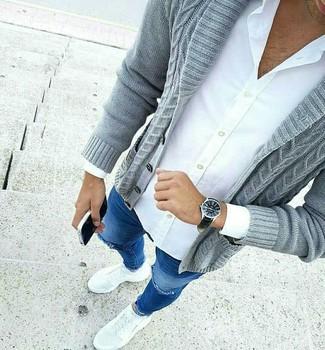 Wie kombinieren: graue Strickjacke mit einem Schalkragen, weißes Businesshemd, blaue enge Jeans mit Destroyed-Effekten, weiße Sportschuhe