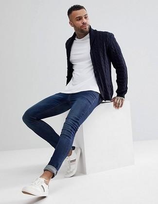 Weiße Leder niedrige Sneakers kombinieren: trends 2020: Kombinieren Sie eine dunkelblaue Strickjacke mit einem Schalkragen mit dunkelblauen engen Jeans für einen bequemen Alltags-Look. Komplettieren Sie Ihr Outfit mit weißen Leder niedrigen Sneakers.