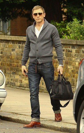 Daniel Craig trägt graue Strickjacke mit einem Schalkragen, weißes T-shirt mit einer Knopfleiste, dunkelgraue Jeans, braune Leder Brogues