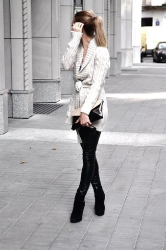 Wie kombinieren: hellbeige Strickjacke mit einem Schalkragen, schwarze Lederleggings, schwarze Keilstiefeletten aus Wildleder, schwarze und weiße Leder Clutch