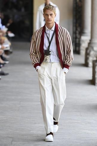 Wie kombinieren: rote und weiße Strickjacke mit einem Schalkragen, weißes vertikal gestreiftes Langarmhemd, weiße vertikal gestreifte Anzughose, weiße Slip-On Sneakers aus Leder