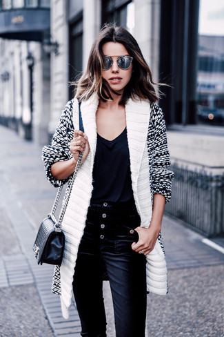 Wie kombinieren: weiße und schwarze Strickjacke mit einem Schalkragen, schwarzes T-Shirt mit einem V-Ausschnitt, schwarze Kordjeans, schwarze gesteppte Leder Umhängetasche