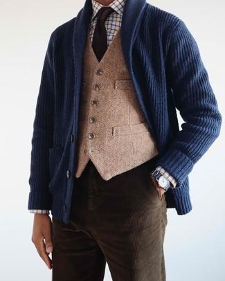Wie kombinieren: dunkelblaue Strickjacke mit einem Schalkragen, beige Wollweste, weißes Businesshemd mit Karomuster, dunkelbraune Kordjeans