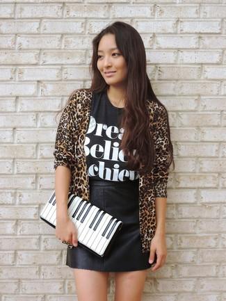 Wie kombinieren: beige Strickjacke mit einer offenen Front mit Leopardenmuster, schwarzes und weißes bedrucktes T-Shirt mit einem Rundhalsausschnitt, schwarzer Leder Minirock, weiße und schwarze bedruckte Leder Clutch