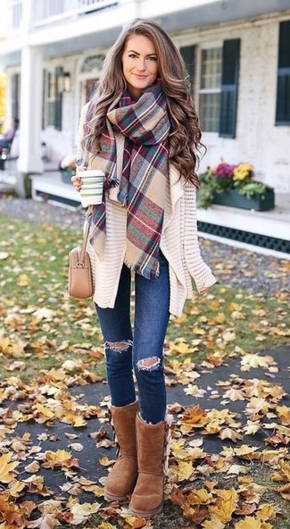 Wie kombinieren: hellbeige Strick Strickjacke mit einer offenen Front, dunkelblaue enge Jeans mit Destroyed-Effekten, braune Ugg Stiefel, hellbeige Leder Umhängetasche