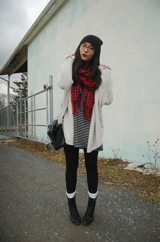 Wie kombinieren: weiße Strick Strickjacke mit einer offenen Front, schwarzes und weißes horizontal gestreiftes Freizeitkleid, schwarze Leggings, schwarze flache Stiefel mit einer Schnürung aus Leder