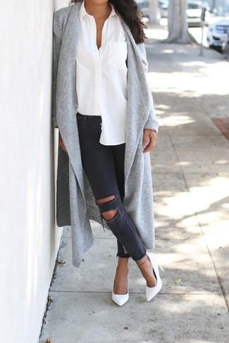Wie kombinieren: graue Strickjacke mit einer offenen Front, weißes Businesshemd, dunkelgraue enge Jeans mit Destroyed-Effekten, weiße Leder Pumps