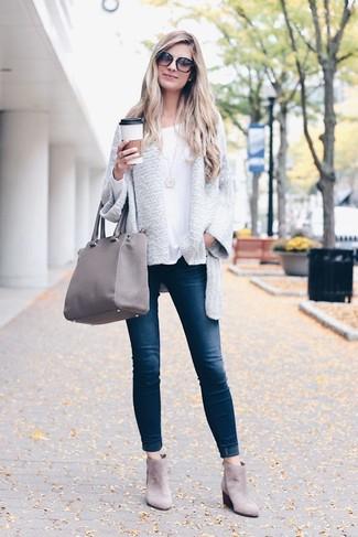 Wie kombinieren: graue Strickjacke mit einer offenen Front, weißes Langarmshirt, dunkelblaue enge Jeans, graue Chelsea-Stiefel aus Wildleder