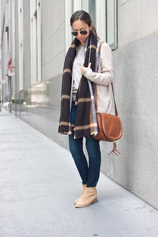 Wie kombinieren: hellbeige Strickjacke mit einer offenen Front, grauer Pullover mit einem Rundhalsausschnitt, dunkelblaue enge Jeans, hellbeige Wildleder Stiefeletten
