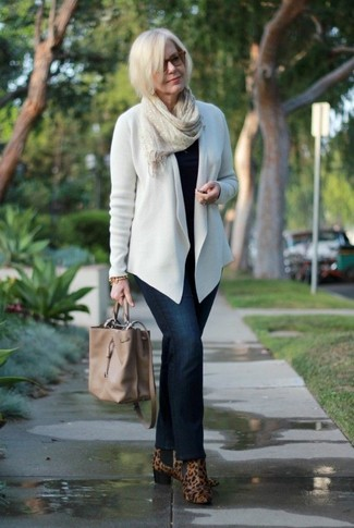 Wie kombinieren: weiße Strickjacke mit einer offenen Front, schwarzer Pullover mit einem Rundhalsausschnitt, dunkelblaue Jeans, braune Wildleder Stiefeletten mit Leopardenmuster