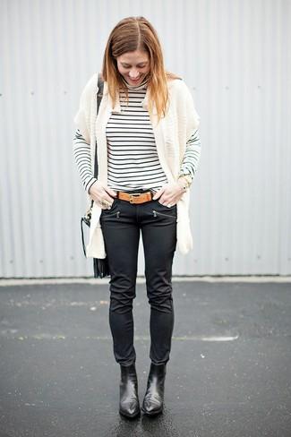Wie kombinieren: weiße Strick Strickjacke mit einer offenen Front, weißer und schwarzer horizontal gestreifter Rollkragenpullover, schwarze enge Jeans aus Leder, schwarze Leder Stiefeletten