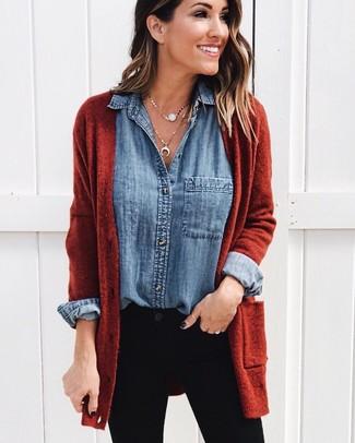 Wie kombinieren: rotbraune Strickjacke mit einer offenen Front, blaues Jeanshemd, schwarze enge Jeans, goldener Anhänger