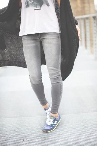 Wie kombinieren: schwarze Strick Strickjacke mit einer offenen Front, weißes und schwarzes bedrucktes Trägershirt, graue enge Jeans, blaue Sportschuhe