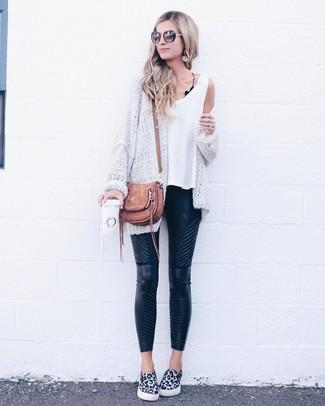 Wie kombinieren: weiße Strick Strickjacke mit einer offenen Front, weißes Trägershirt, schwarze gesteppte enge Hose aus Leder, weiße und schwarze Slip-On Sneakers mit Leopardenmuster